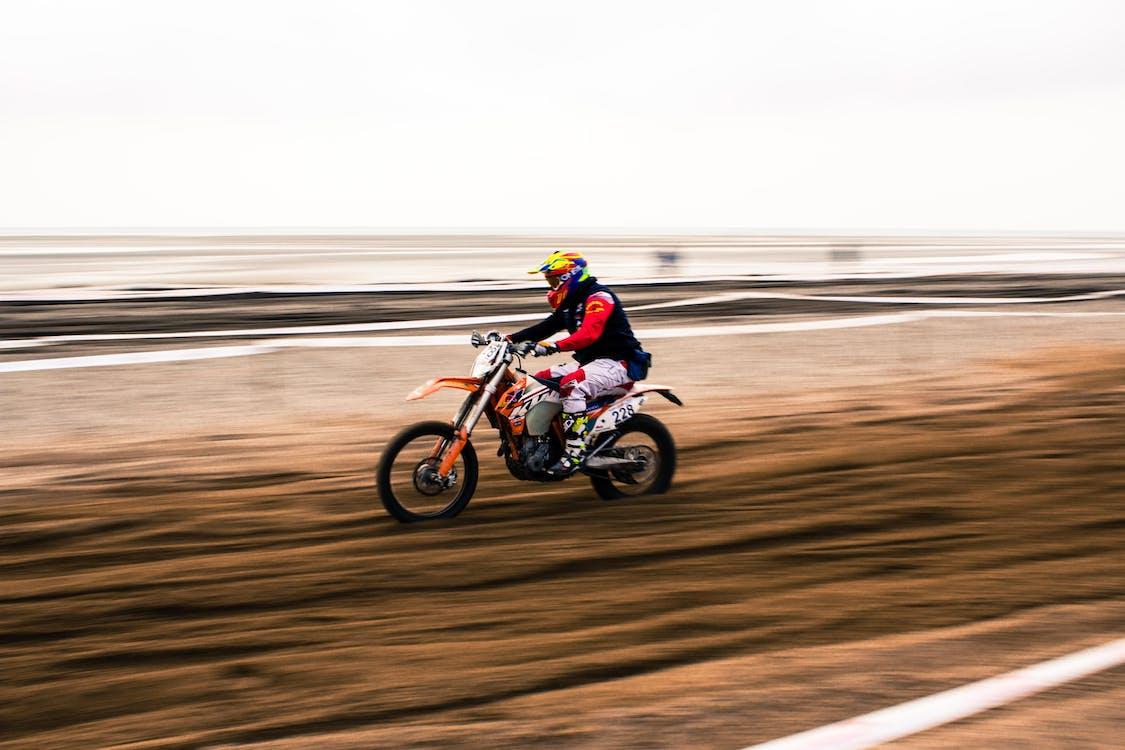 Man Riding Motocross Dirt Bike on Road