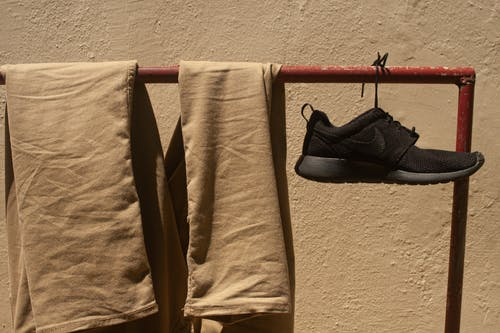 Brown Pants and Black Shoe Hanging on Red Metal Rack