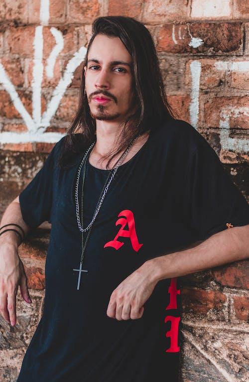 Man in Black Crew Neck T-shirt Standing Beside Brown Brick Wall