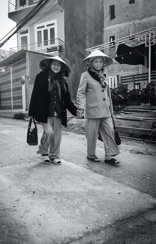 Grayscale Photo of Women Walking on Sidewalk Holding Hands