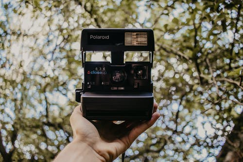 Black Polaroid Camera on Persons Hand