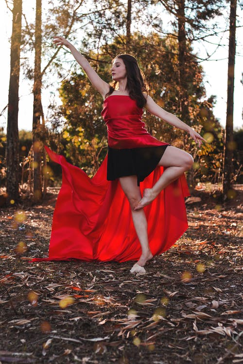 Full body of young slim barefoot female dancer in bright dress standing on one leg with raised arm and looking away while performing ballet pose on dry terrain behind trees