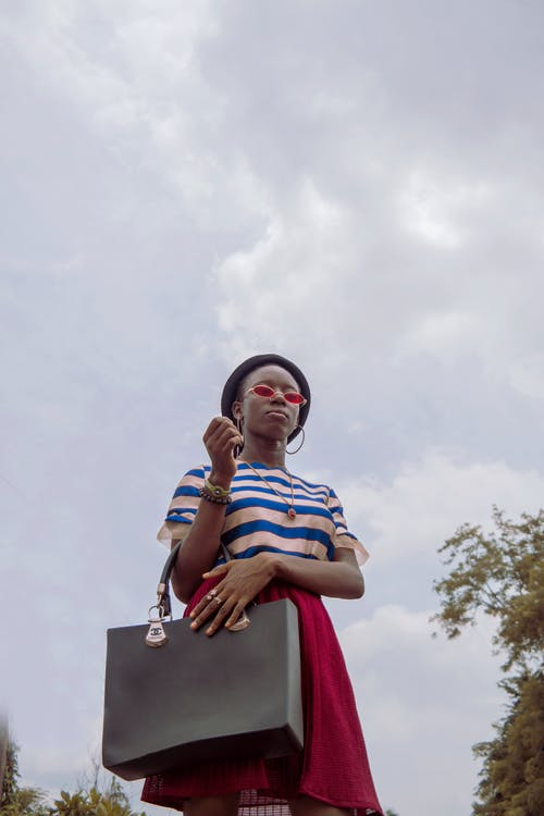 From below of fashionable young African American lady in trendy outfit and sunglasses standing in park with bag in hand against cloudy sky