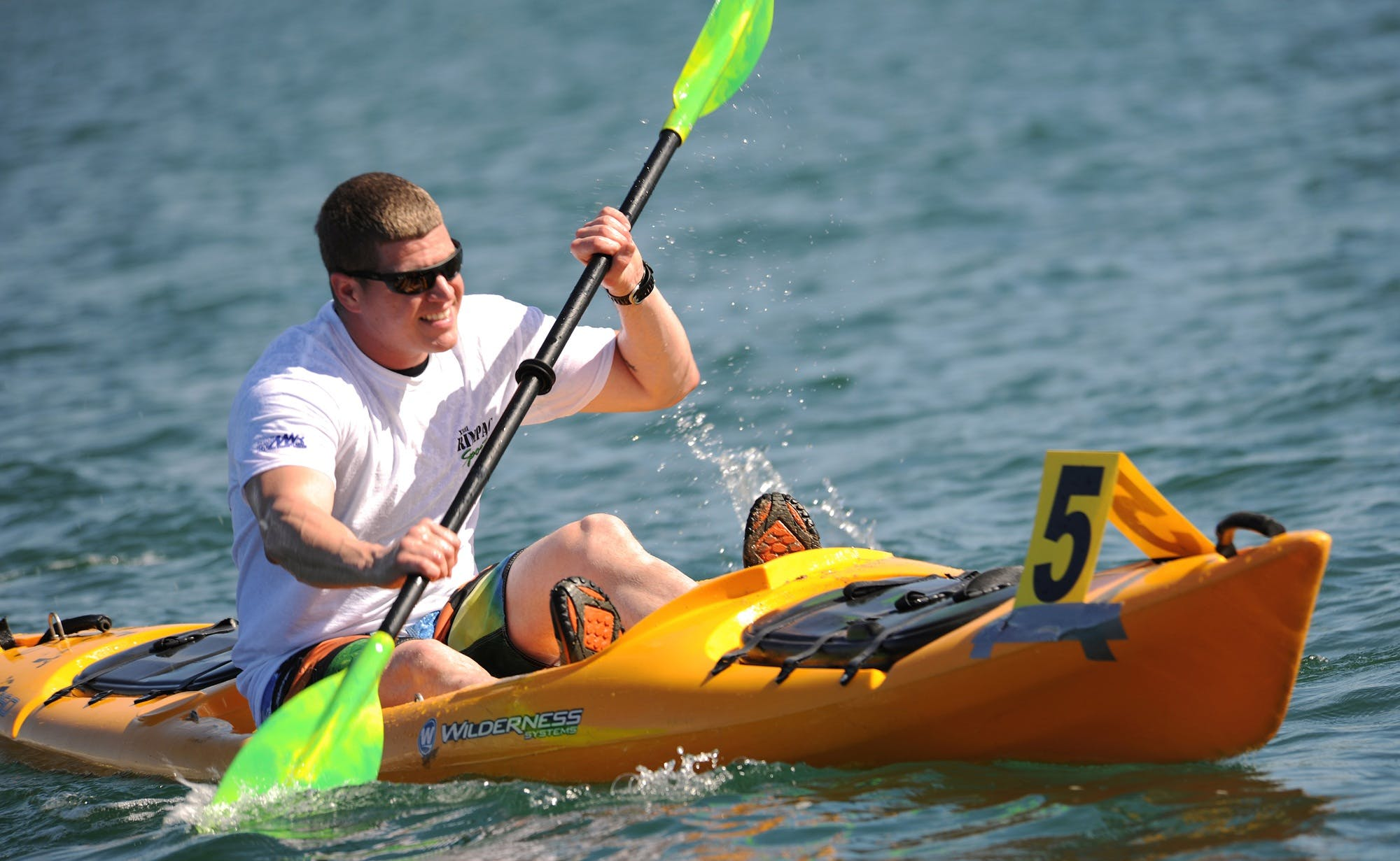 Smiling Man in White Crew Neck T Shirt Wearing Sunglasses Paddling on Yellow Kayak during Daytime
