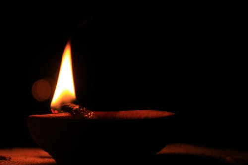 Luminous flame of burning wooden twig on round shaped bowl on table at silent night on black background