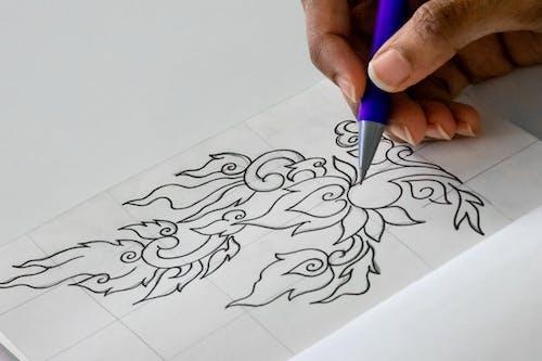 Crop artist drawing on paper sheet in workshop