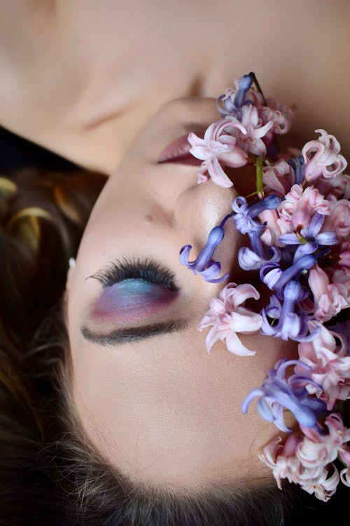 From above of female with makeup on eyelids and lips lying with bright blossoming flowers with gentle petals covering half face