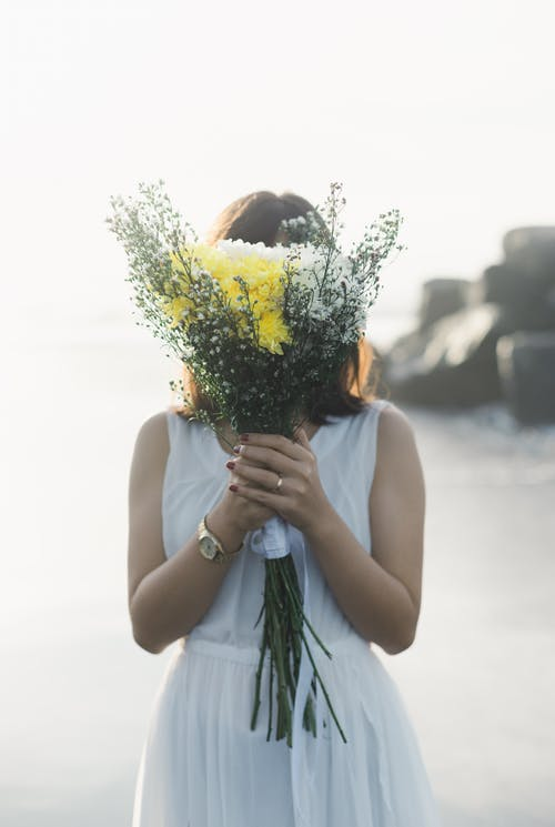 Woman in White Tank Top Holding Yellow Sunflower Bouquet