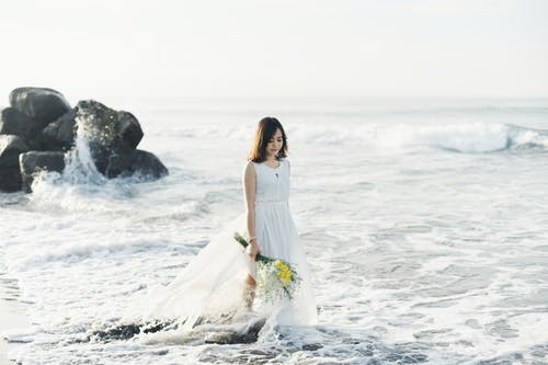Woman in White Dress Standing on Rock Formation Near Sea