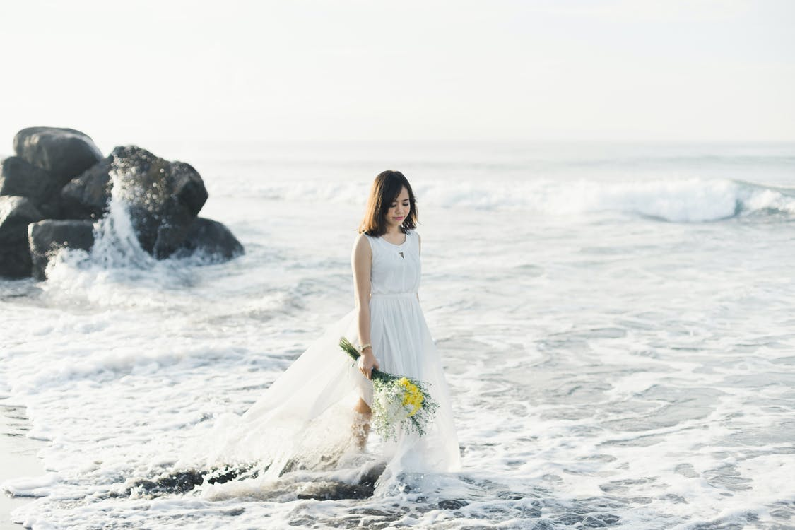 Ethnic bride walking in foamy sea with bridal bouquet