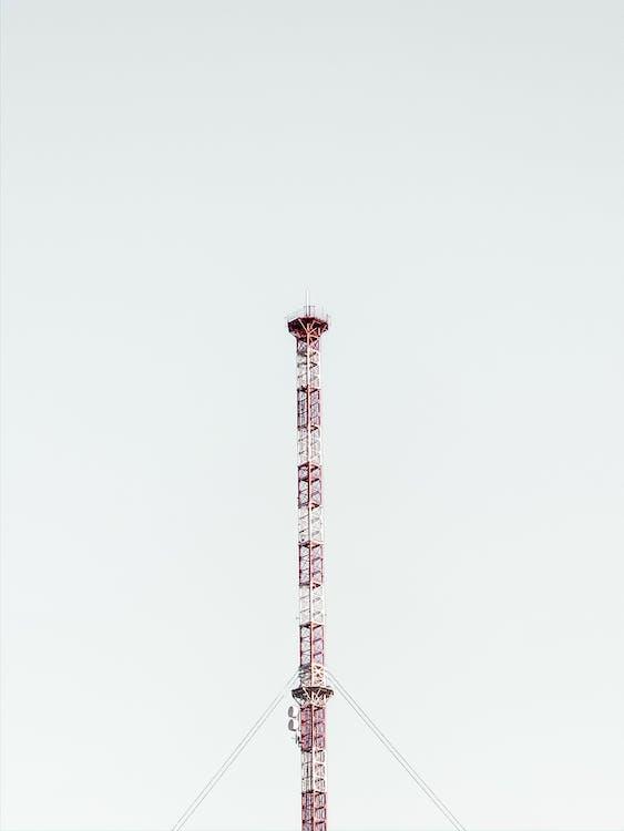 Telecom tower located under gray sky