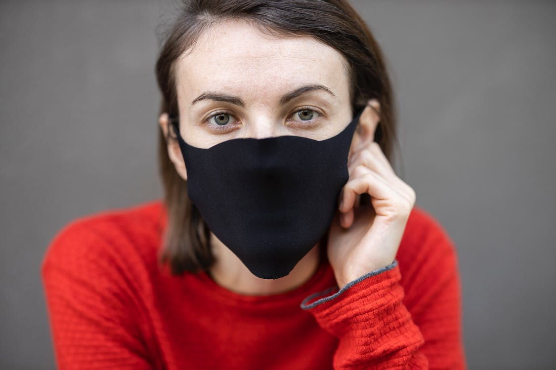 Woman in Red Sweater Covering Her Face With Black Mask