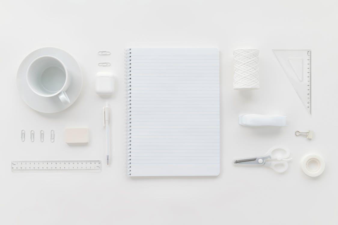 White Notebook Beside Silver Scissors and White Ceramic Mug