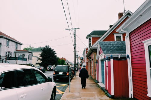 Back view of anonymous person in outerwear strolling along street with parked cars and residential cottages in suburb on overcast weather