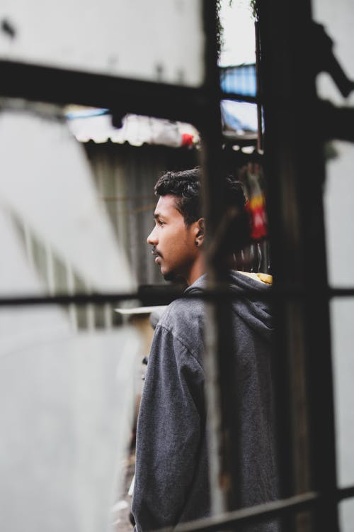 Side view of young ethnic guy in casual clothes standing outside window with broken glass and looking away pensively on street on daytime