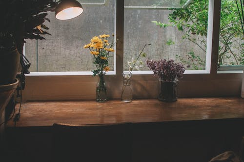 Flowers in vases with burning table lamp on windowsill