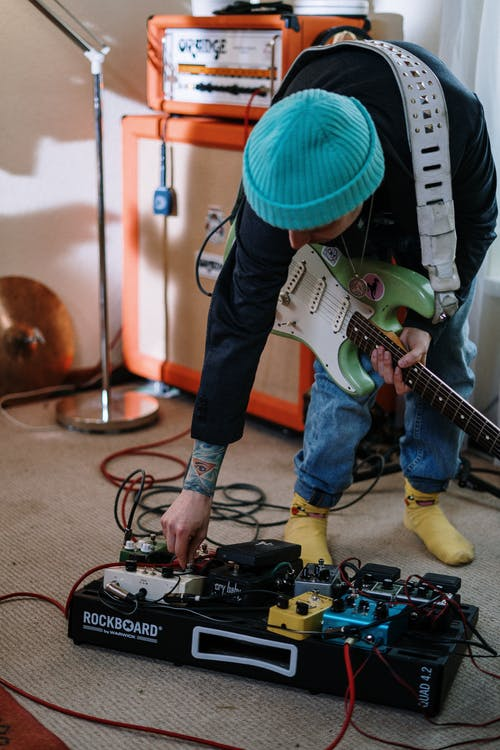 Person in Green Hat Playing Electric Guitar
