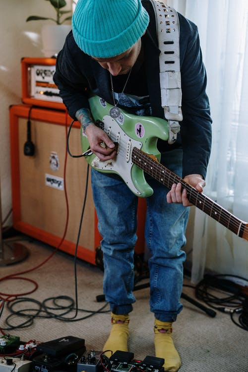 Person in Blue Denim Jeans Holding White Electric Guitar
