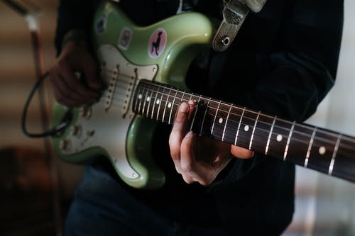 Person Holding White and Red Electric Guitar