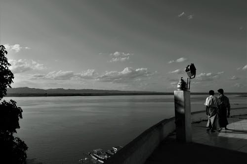 Person Standing on Wooden Dock in Grayscale Photography