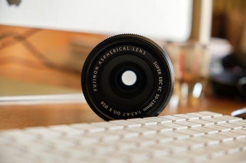 Black Nikon Camera Lens on White Computer Keyboard