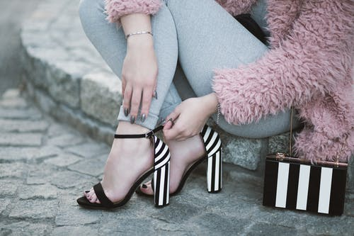 Anonymous woman in stylish shoes with striped handbag sitting on pavement and fastening thin straps on trendy high heeled sandals on daytime