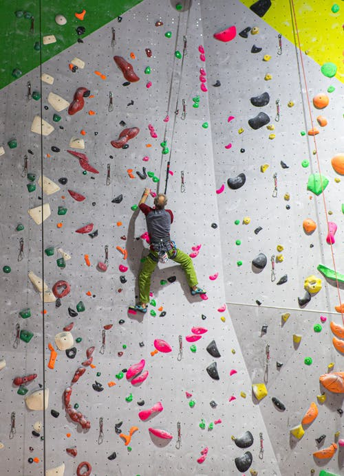 Unrecognizable male boulderer climbing on wall