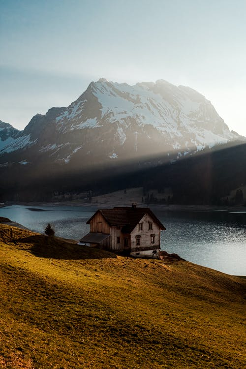 White and Brown House Near Body of Water and Snow Covered Mountain