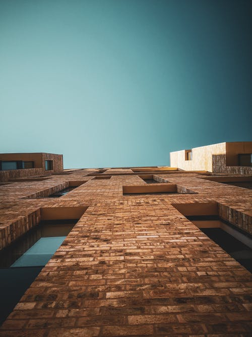 From below of brick wall of contemporary residential building with narrow and high windows against cloudless turquoise sky on sunny day