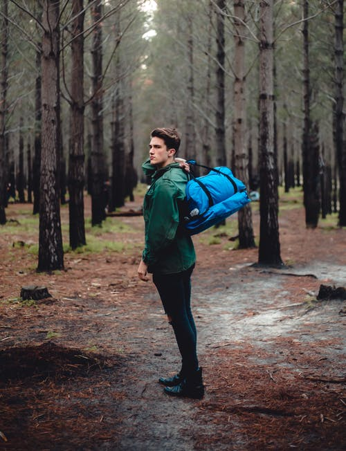 Young man with big bag in leafless forest