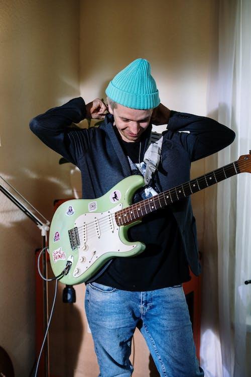 Man in Black Jacket Playing Electric Guitar