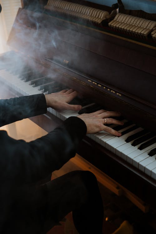 Person in Black Pants Playing Piano
