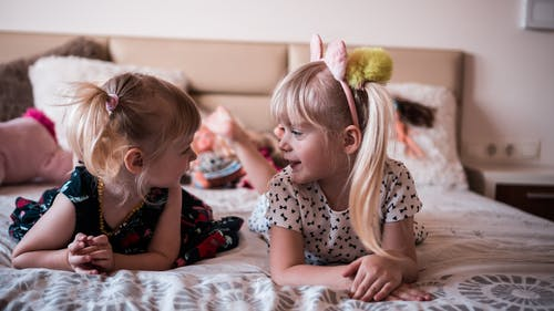 Cute little sisters resting on bed and chatting