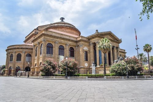 Low angle exterior of aged classic stone building of Teatro Massimo with columns and ornamental elements located square in Palermo
