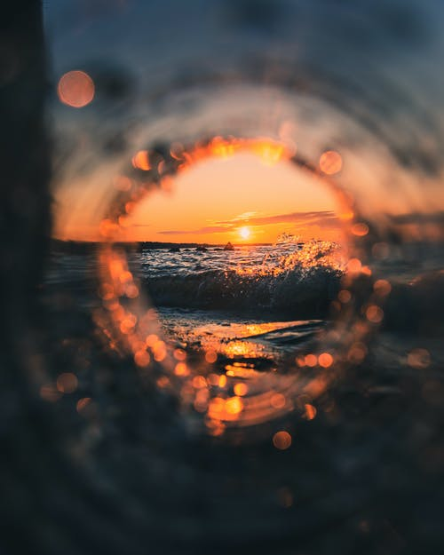 Bright sunset over picturesque ocean with waves splashing against rocky shore through round glass hole