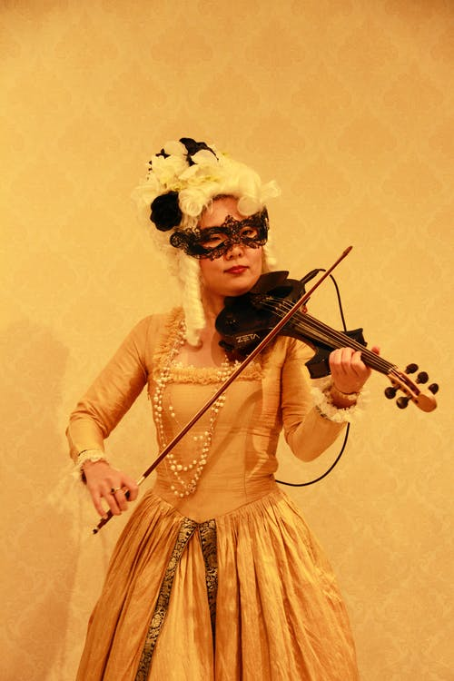 Woman in White Long Sleeve Dress Playing Violin