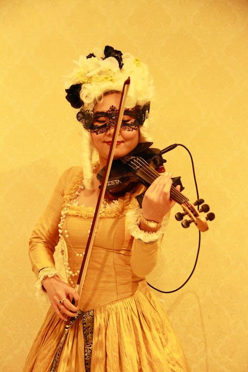 Woman in Yellow Long Sleeve Shirt Playing Violin