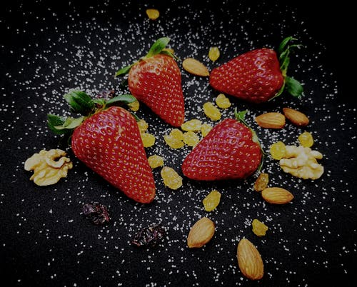From above of ripe delicious sweet strawberries and raisins served on black plate with scattered healthy almonds and walnuts decorated with white seeds