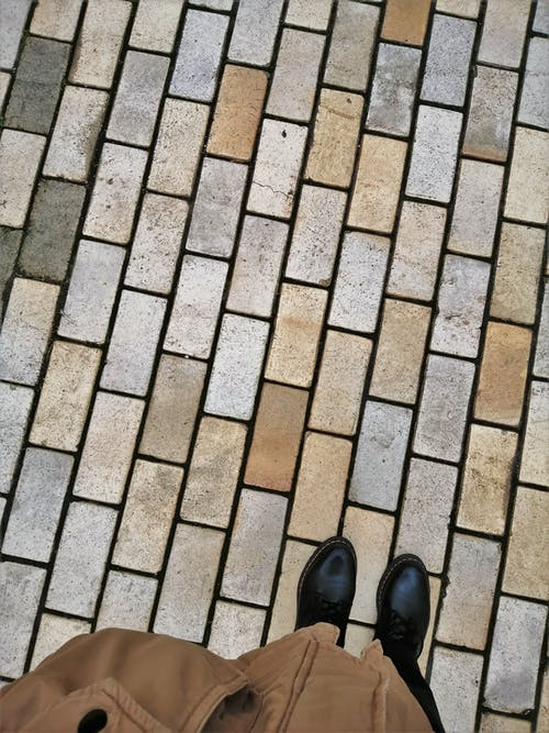 Person in Black Leather Shoes Standing on Brown Brick Floor