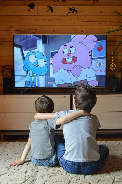 Back view of anonymous adorable little siblings cuddling while sitting on floor and watching funny cartoon on TV at home