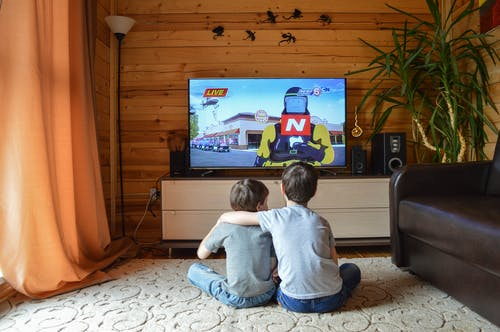 Faceless little boys entertaining with TV at home