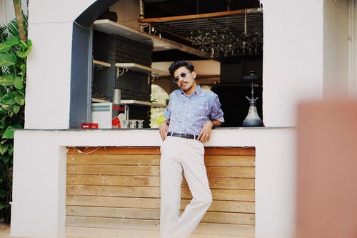 Trendy young Indian man resting near counter of summer cafe
