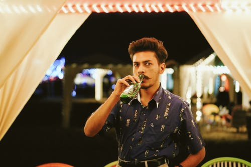 Concentrated young Indian man drinking beer in park cafe at night
