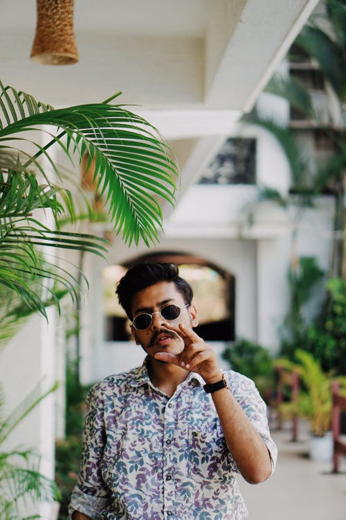 Trendy young Indian man chilling in backyard of modern building in tropical country