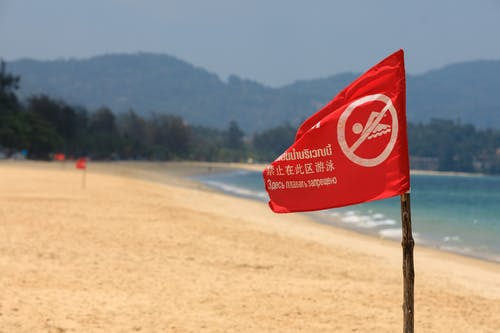 Red and White Flag on Brown Wooden Pole Near Sea