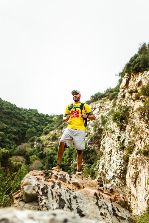 Happy young mountaineer recreating on rock with breathtaking view of valley