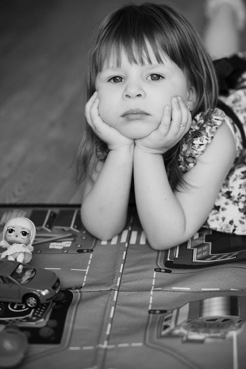 Fotos de stock gratuitas de aburrido, Acostado, blanco y negro, niña