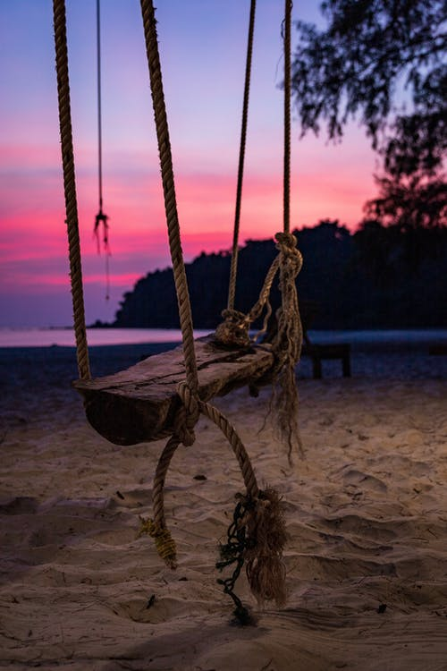 Old swing hanging on rope on sandy beach during picturesque sunset
