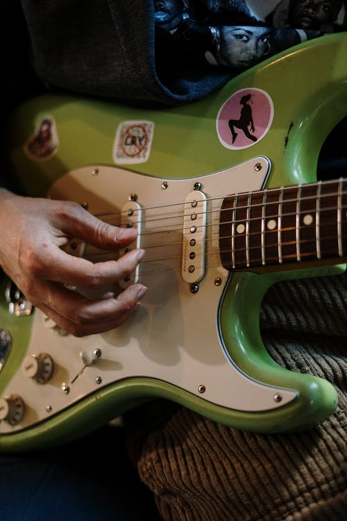 Person Playing Green and White Electric Guitar