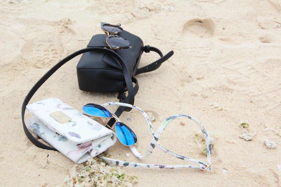 Foto profissional grátis de alforjes, areia da praia, bolsas